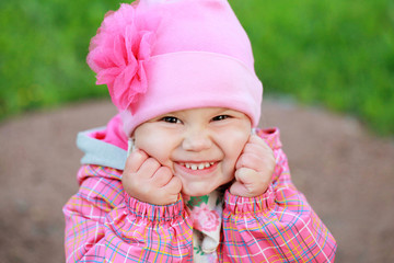 Funny laughing Caucasian baby girl in pink, outdoor portrait