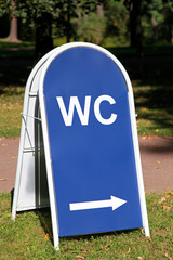 Blue metal street banner with arrow and WC mark