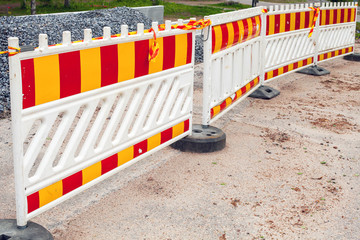 Striped red and yellow road barriers, area under construction