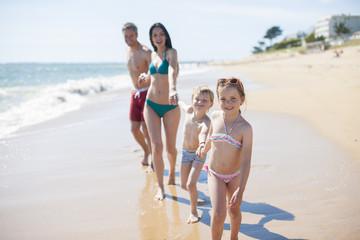 happy family in swimsuit having fun in the beach