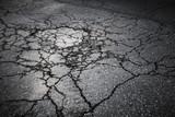 Dark asphalt road with cracks. Background texture