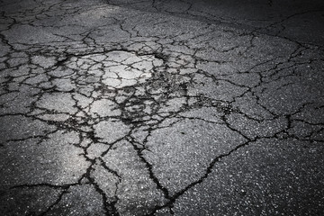 Dark asphalt road with cracks. Background texture