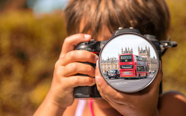 Young girl taking photos of London Bus by professional digital c