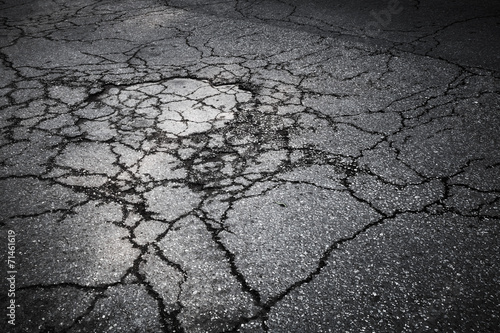 Dark asphalt road with cracks. Background texture - 71461619