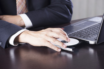 Business man insert disk to laptop