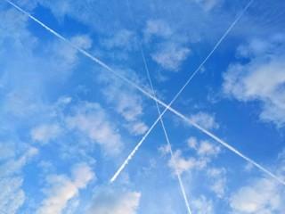 3 Kondensstreifen kreuzen sich am Himmel zu einem Dreieck.