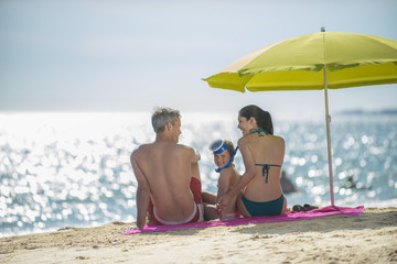 family in swimsuit at the beach sitting under a beach umbrella t