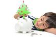Little boy saving money in piggy bank