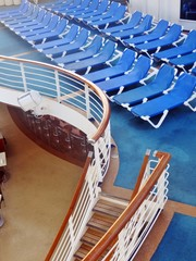 Blue lounge chairs on a cruise ship deck