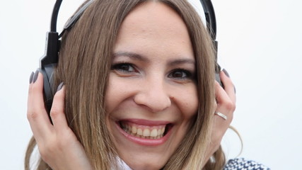 Happy flirty girl young woman with headphones listening to music