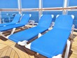 Lounge chairs on a cruise ship deck overlooking the ocean