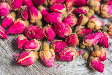 Dried tea rose buds on old wooden background