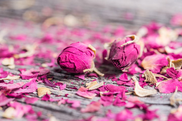 two rose buds  and petals on old wooden table