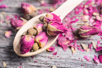 wooden spoon with tea rose buds and petals on old wooden table