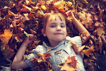 adorable girl in a sweater lying on autumn leaves in the park