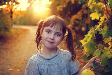happy and smiling girl in braids in the autumn afternoon