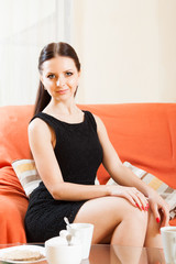 charming young lady in black on  sofa