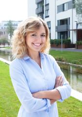 Frau mit blonden Locken vor ihrer Wohnung