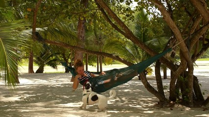Young Woman in Hammock Playing with a Dog.