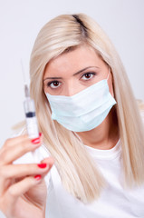 Female doctor or nurse in medical mask holding syringe with inje