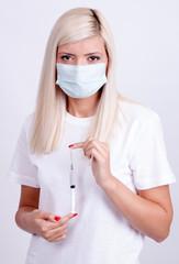 Female doctor or nurse in medical mask holding syringe with inje