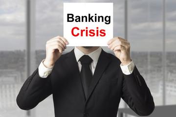 businessman hiding face behind sign banking crisis
