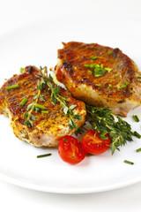 Fresh roasted pork steaks on white plate