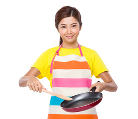 Housewife cooking with pan and spatula