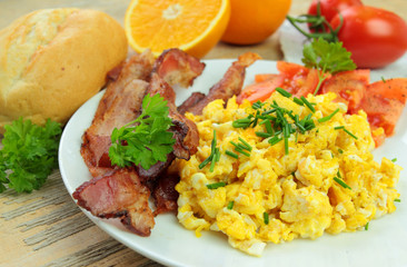 Breakfast with scrambled eggs with chive, bacon and tomatoes