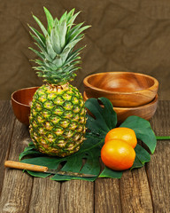 Still Life with Pineapple and Oranges on Wooden background.
