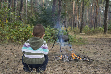 The child sits in the woods near the fire, where the food is coo