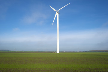 White wind turbine in a sunny meadow at fall