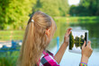 young girl taking photo of the lake by tablet pc