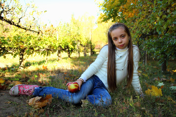 Girl  sitting in a park  with an apple in his hand.