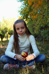 Girl with long hair sitting  with an apple in his hand.