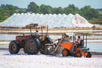 Sea salt production. Salt evaporation pond with tractor.