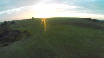 Aerial view. Flight of the camera towards the setting sun fall.