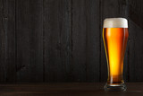 Glass of beer on wooden table, dark background