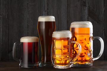 Beer glasses with various beer on table, dark wooden background