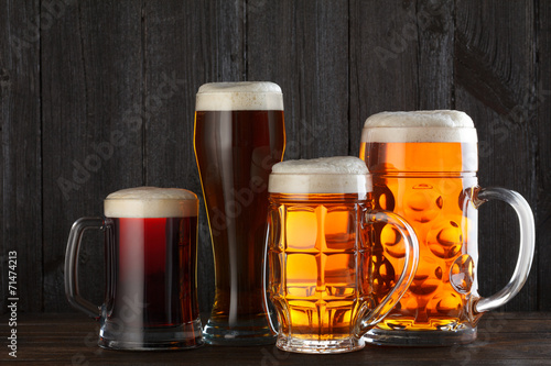 Beer glasses with various beer on table, dark wooden background - 71474213