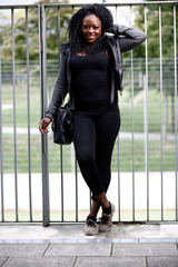 Smiling Black Woman Posing at Gray Gate