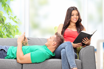 Couple relaxing seated on a couch at home