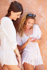 Female Friends On Holiday Together Using Mobile Phone