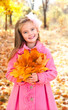 Autumn portrait of adorable little girl with maple leaves