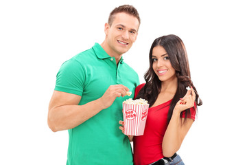 Young couple eating popcorn