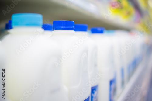 Leinwandbild Motiv Bunch of milk bottles on fridge shelf in supermarket