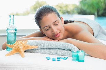Woman lying on massage table at spa center