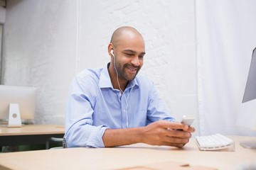 Businessman listening music with mobile phone at desk