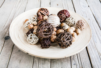 Decorative twig spheres lay in wooden bowl on wooden table