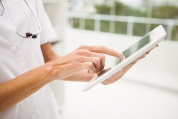 Close-up of doctor using digital tablet in medical office